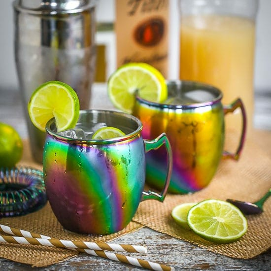 Two Moscow Mules served in rainbow mugs with lime slices with a cocktail shaker, striped straws, ginger beer, and vodka scattered around.