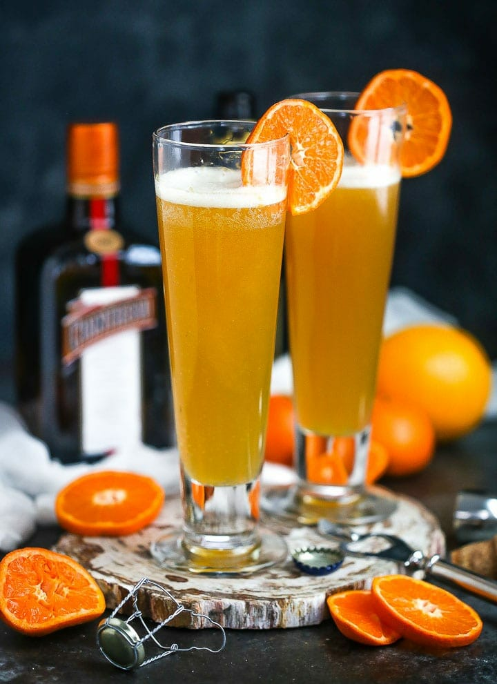 Two glasses of the The Mustache (aka the Manly Mimosa) garnished with orange slices, and orange slices, a champagne top and the bottle of cointreau are around.