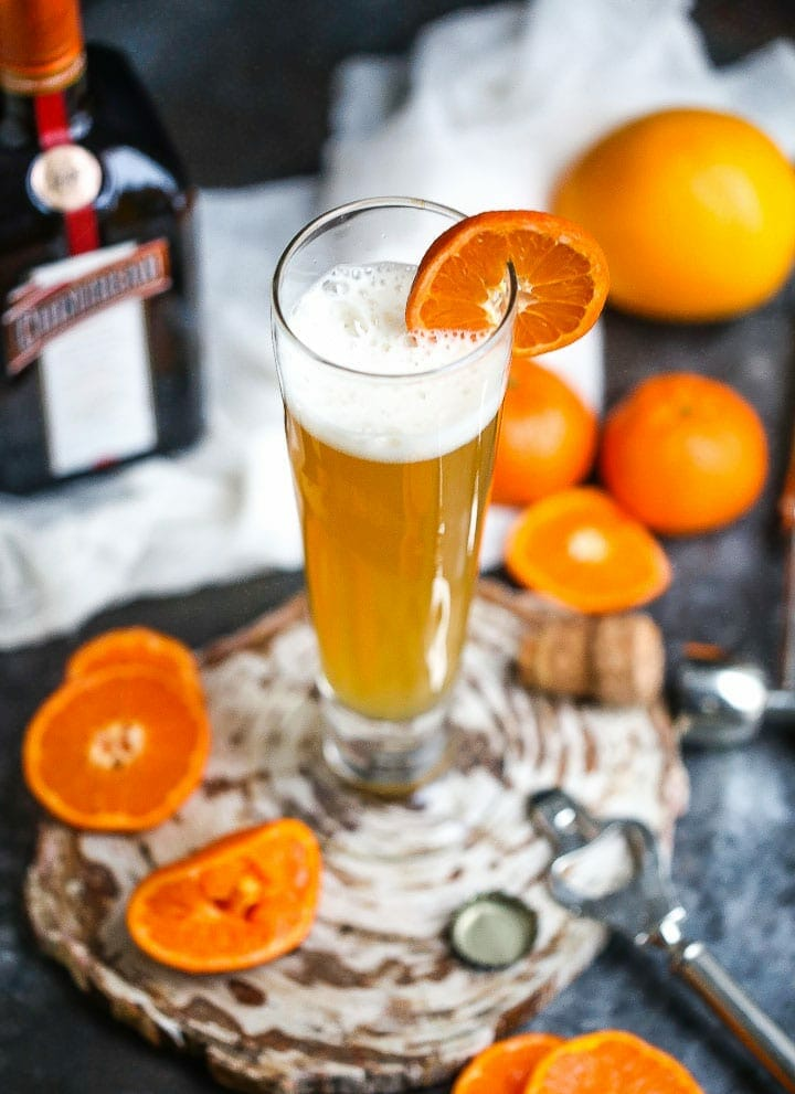 A glass of the The Mustache (aka the Manly Mimosa) garnished with orange slices, and orange slices, a champagne top and the bottle of cointreau are around.