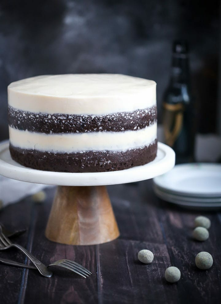 Chocolate Stout Cake with Baileys Buttercream on a cake stand with candies and forks scattered around and a stack of plates in the background.