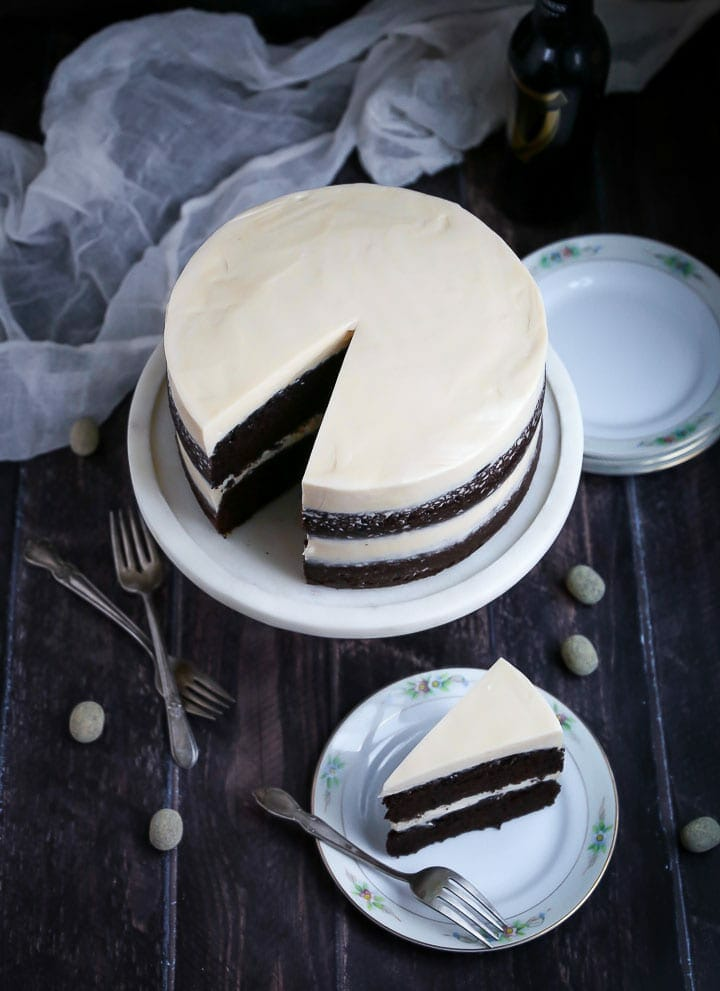 Chocolate Stout Cake with Baileys Buttercream with a slice cut out on a cake stand and the cake slice on a plate with a fork.