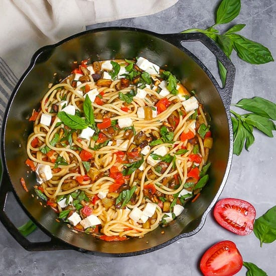 Overhead shot of roasted eggplant pasta in a cast iron dutch oven garnished with fresh basil, with basil and a sliced tomato alongside.