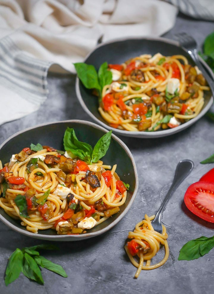 Two black bowls of roasted eggplant pasta with a few basil leaves garnishing the bowls and a fork with a twirl of pasta alongside.