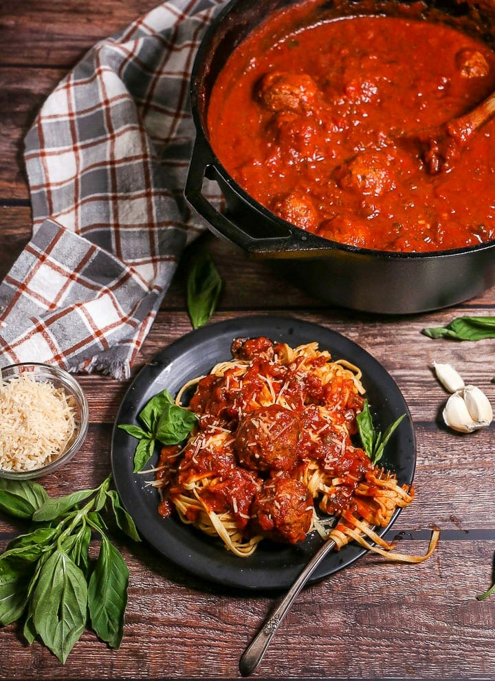 A serving of Sunday Sauce and Meatballs over fettuccine on a black plate garnished with fresh basil and a fork twirled in the pasta. The pot of sauce is in the corner.
