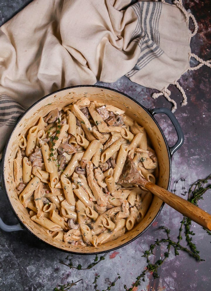 Creamy Goat Cheese Pasta with Chicken and Mushrooms in a dutch oven with a wooden spoon in to stir, thyme sprigs scattered around and beige blue striped dish towel.