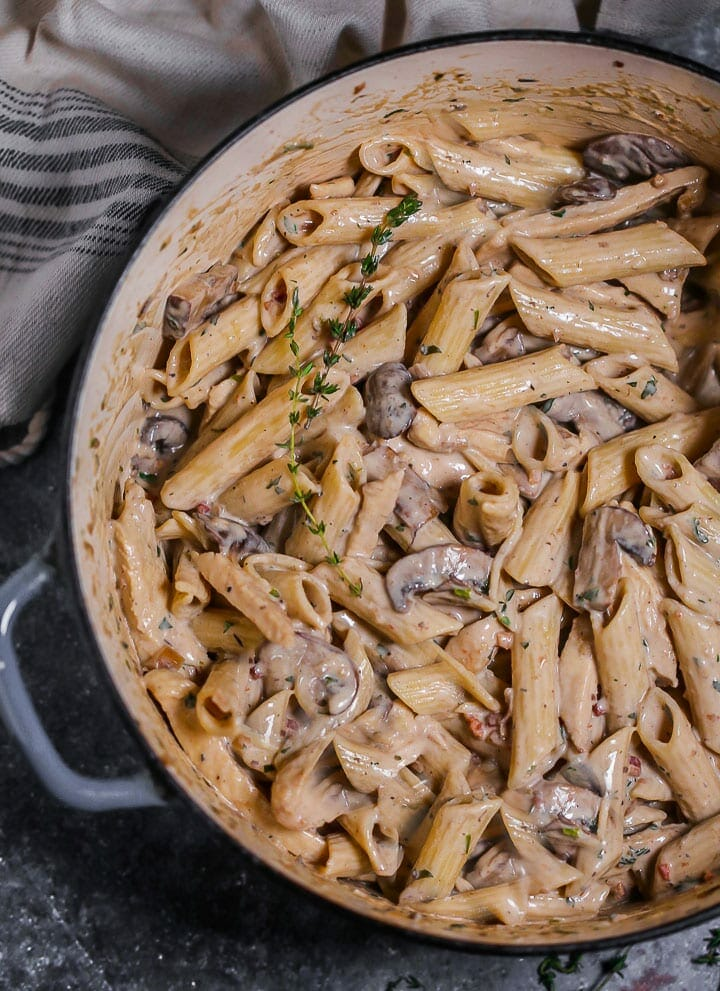 Overhead shot of Creamy Goat Cheese Pasta with Chicken and Mushrooms in a blue enameled dutch oven.