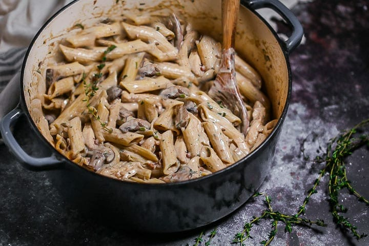 Creamy Goat Cheese Pasta with Chicken and Mushrooms in a blue enamled dutch oven with a wooden spoon in the pot to stir and a few thyme sprigs scattered around.