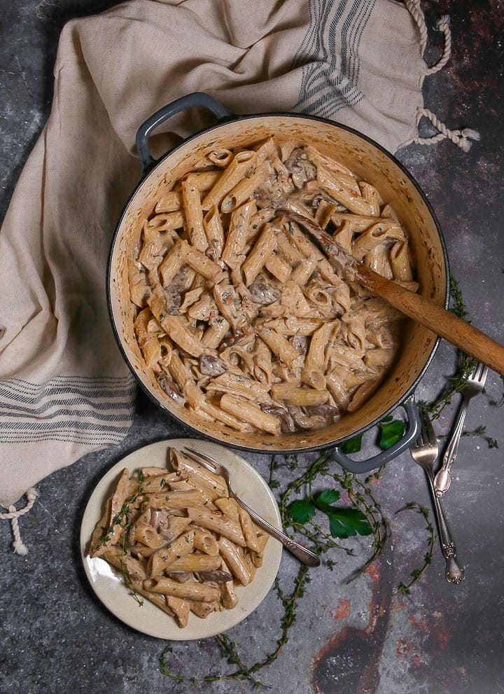 Overhead shot of Creamy Goat Cheese Pasta with Chicken and Mushrooms in a pot with a wooden spoon and a serving on a small plate with forks and thyme scattered around.