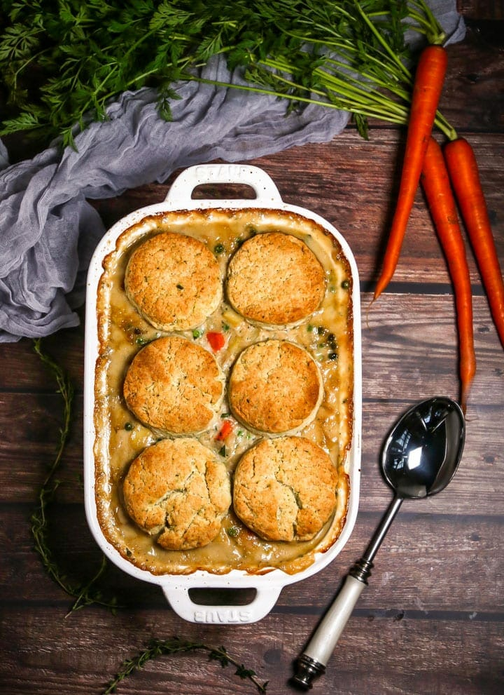 Vegetable Pot Pie with Biscuit Topping in a white baking dish with carrots and a spoon alongside.