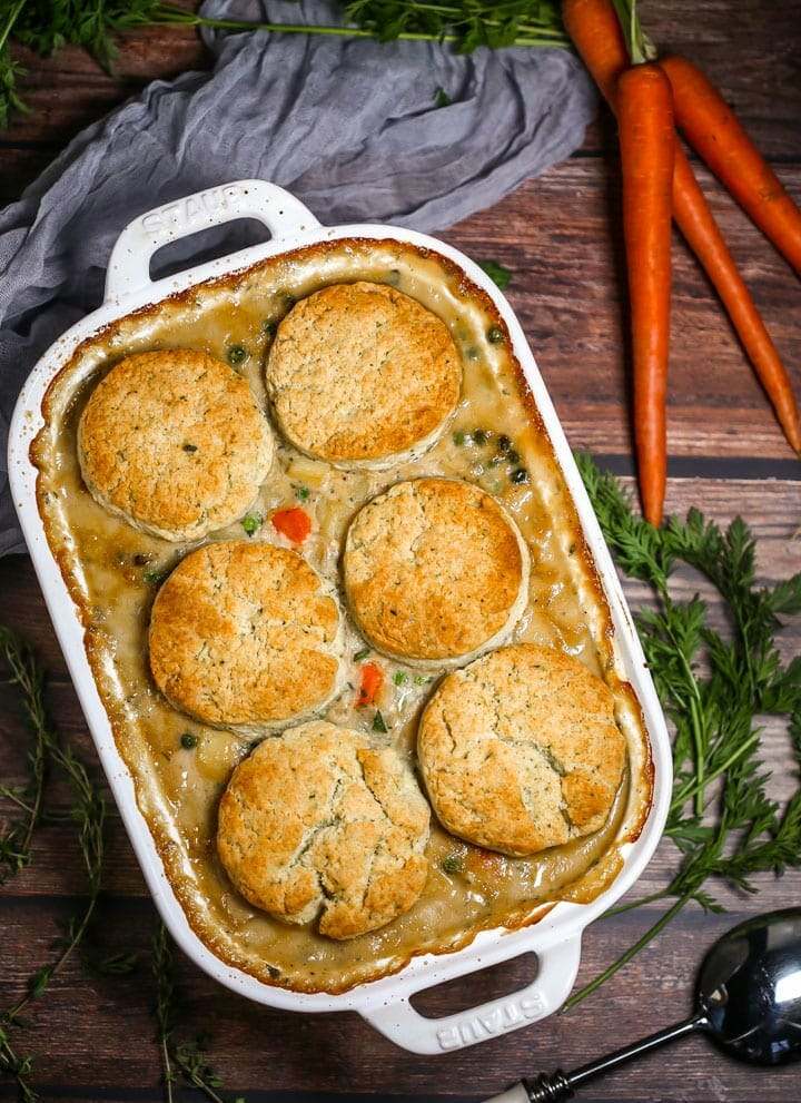 Vegetable Pot Pie with Biscuit Topping in a white baking dish with carrots alongside.