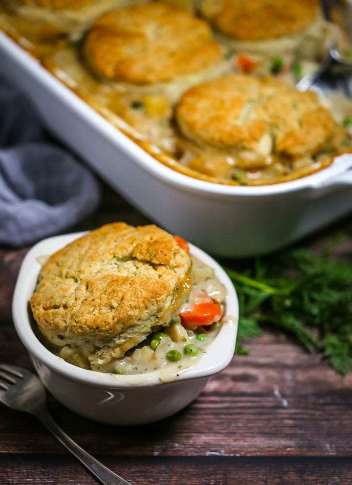 Vegetable Pot Pie with Biscuit Topping in a white baking dish with a serving in a small white bowl.