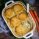 Vegetable Pot Pie with Biscuit Topping in a white baking dish with a portion scooped out with a spoon and carrots on the side.