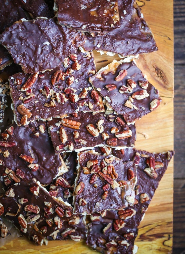 Toffee matzo brittle is topped with chocolate and toasted pecans and piled on a wood board.