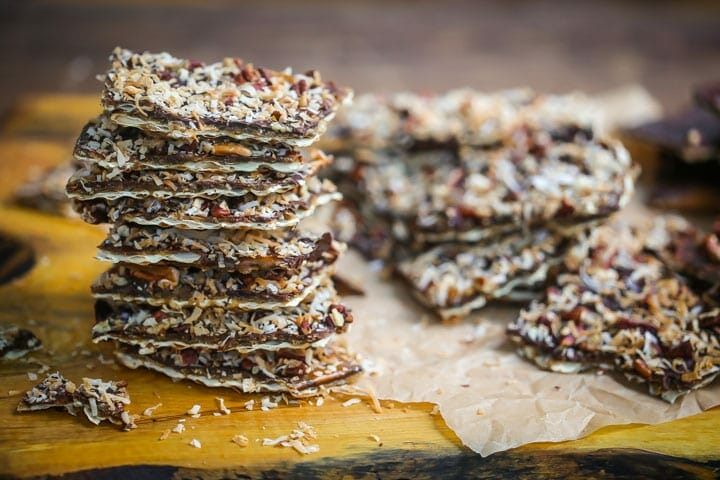 Toffee Matzo Brittle (aka matzo crack), is topped with toasted coconut and pecans is stacked on top of a wood board.
