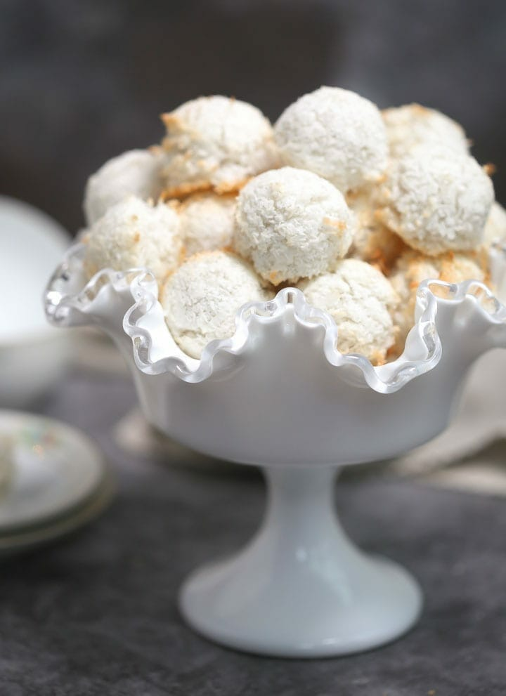A pile of coconut macaroons in a white footed, fluted bowl.