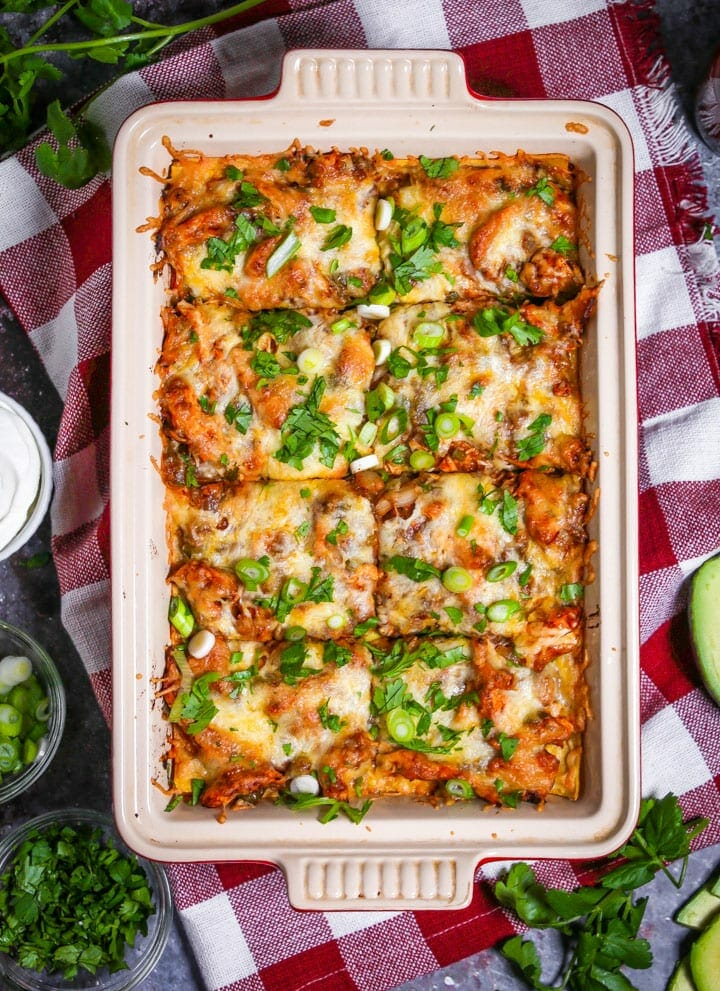 Easy Chicken Enchilada Casserole in a baking dish sprinkled with scallions and cilantro and cut into 8 servings.