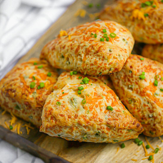 Cheddar Chive Scones on a wood board sprinkled with chives.