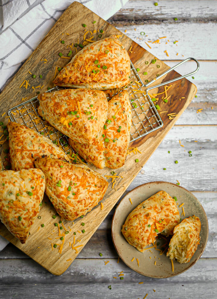 Cheddar Chive Scones on a wood board and a scone pulled apart on a small serving plate.