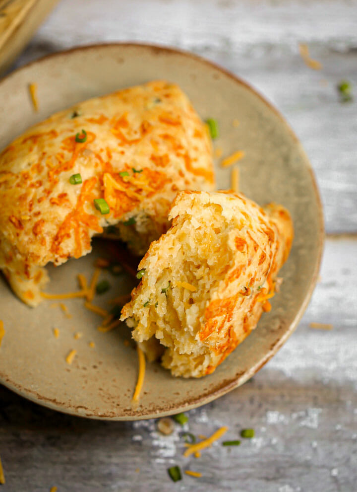 Cheddar Chive Scone pulled apart on a small serving plate.