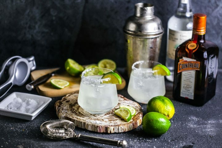 Two margaritas garnished with salt and lime slices, with a cocktail shaker, liquor, and limes scattered around.