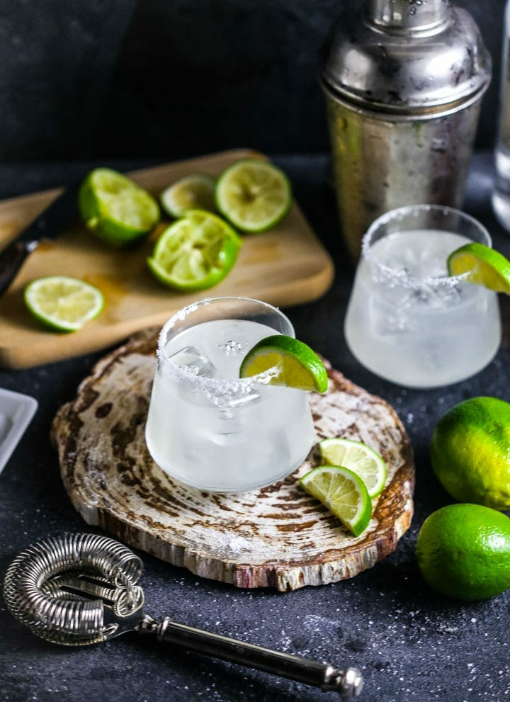 Two margaritas garnished with salt and lime slices, with a cocktail shaker, strainers and limes scattered around.
