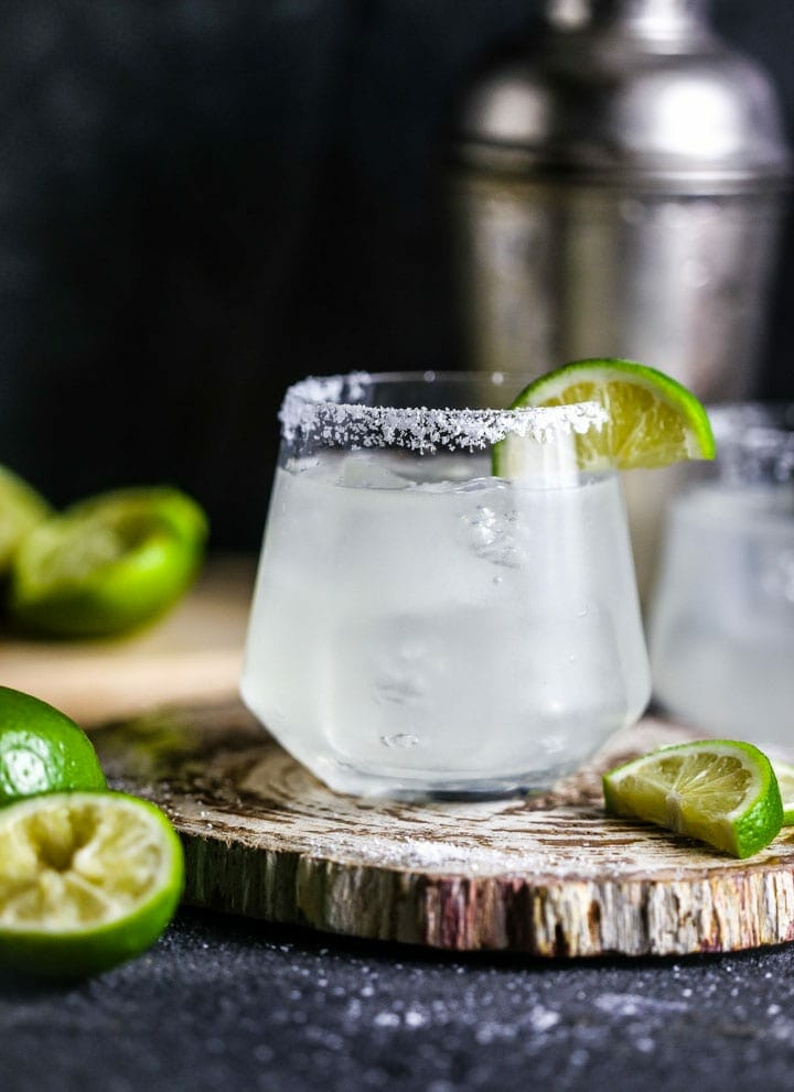 Close up a of a classic margarita garnished with salt and lime.