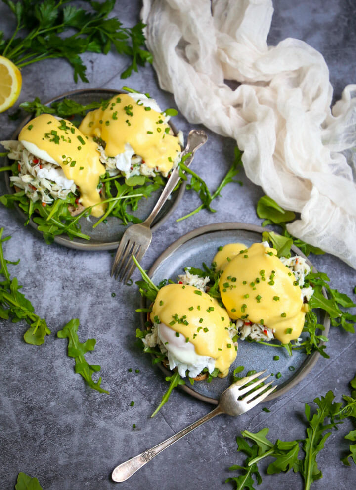 Two servings of Crab Eggs Benedict on round blue plates garnished with minced chives, with forks, fresh arugula and a white gauzy towel on the table.