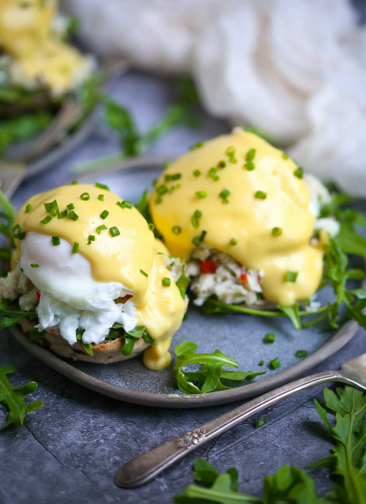 A serving of Crab Eggs Benedict on a round blue plate garnished with minced chives.