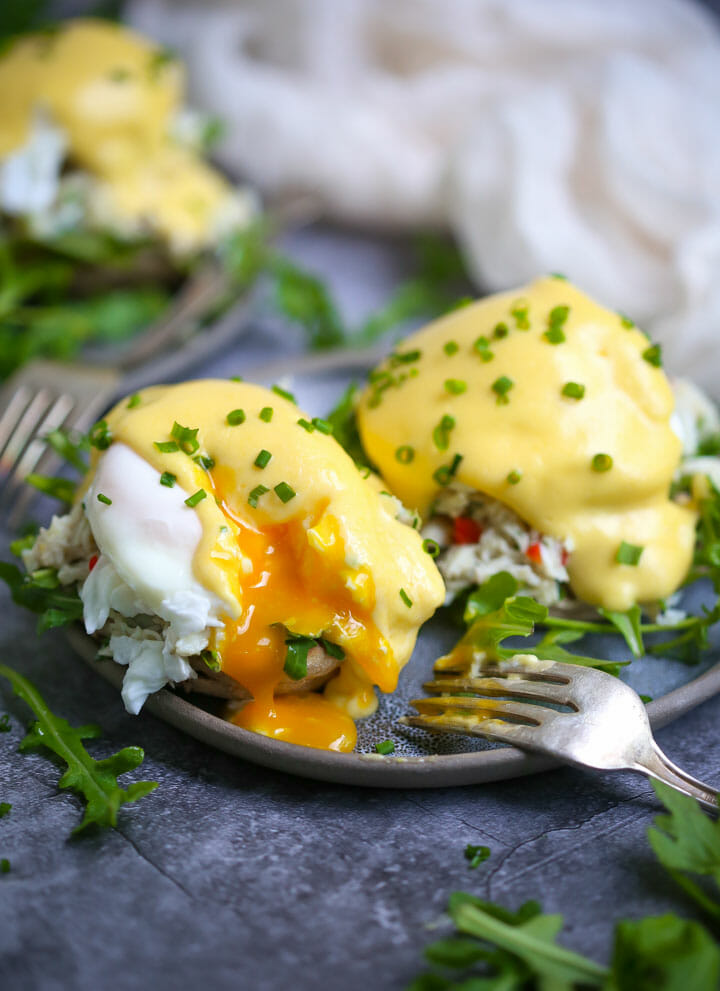 Crab eggs benedict on a round blue plate with a bite taken out and the yolk spilling out.