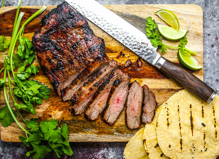 Grilled and rested carne asada, being sliced on a cutting board with cilantro, tortillas and limes scattered around.