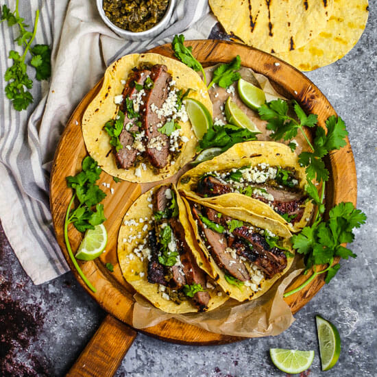 Carne Asada Tacos on a round wooden board with cilantro, limes, grilled tortillas and onion relish scattered around.