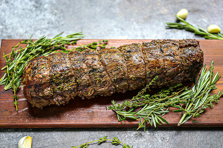 Herb Crusted Grilled Beef Tenderloin on a cutting board with herbs and garlic scattered around.