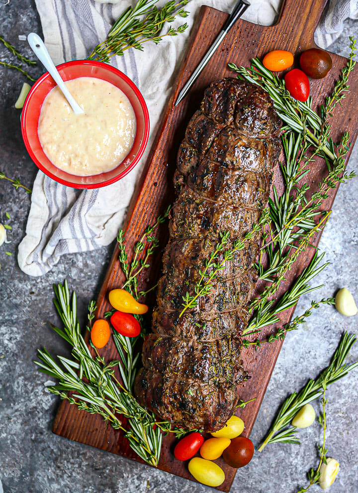 Herb Crusted Grilled Beef Tenderloin on a cutting board with herbs, grape tomatoes, and garlic scattered around and a meat probe and horseradish sauce alongside.