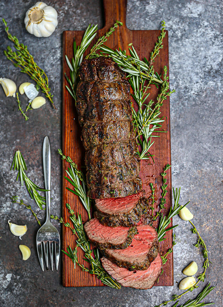 Herb Crusted Grilled Beef Tenderloin partially sliced on a cutting board with herbs and garlic scattered around.