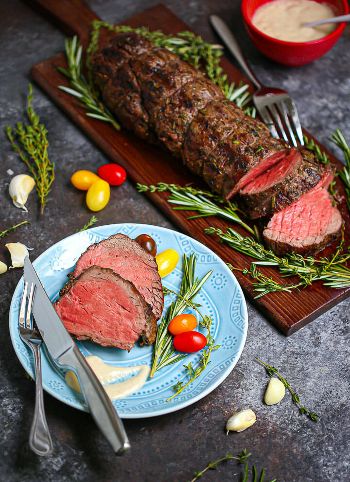 An Herb Crusted Grilled Beef Tenderloin partially carved on a cutting board with two slices on a round blue plate.