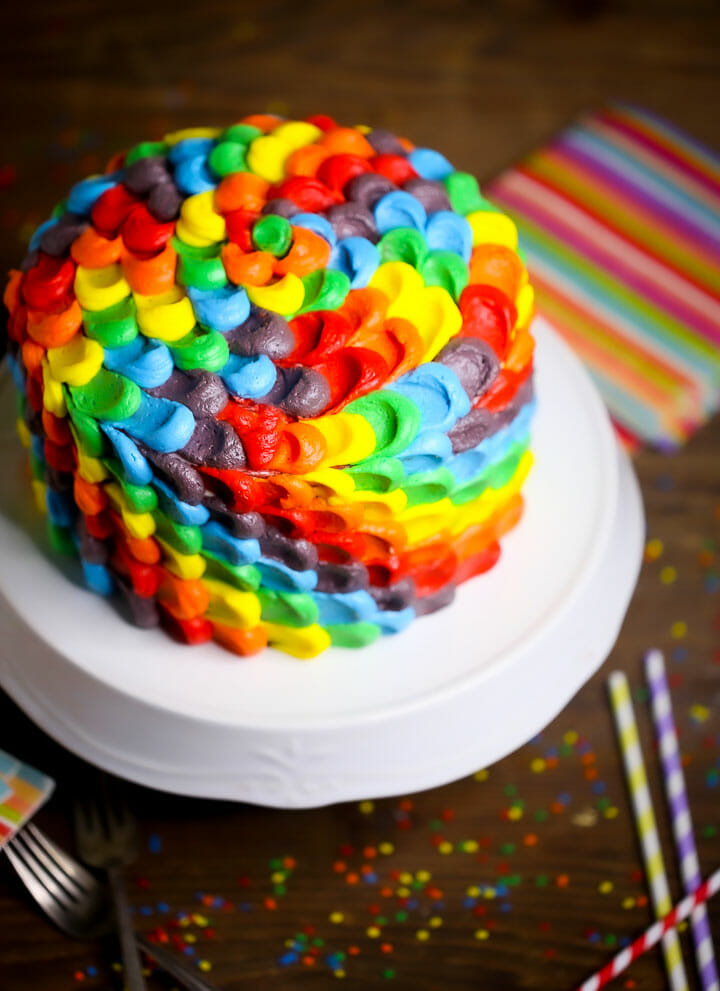 Rainbow Layer Cake on a white cake stand with rainbow napkins, sprinkles, and straws.