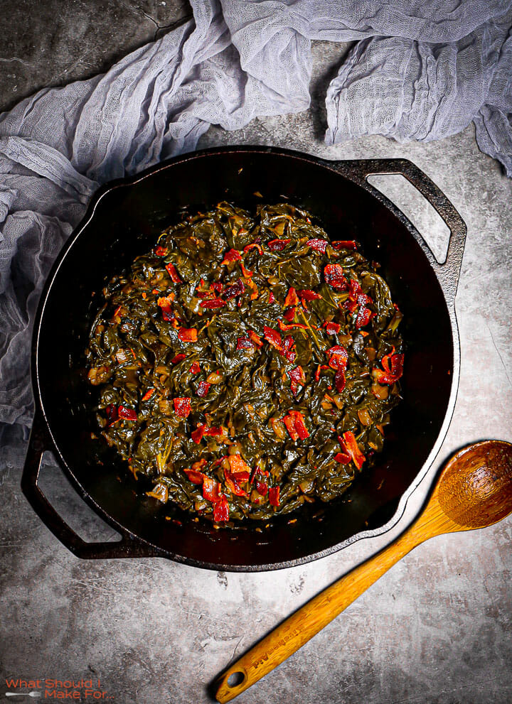 A close up shot of Braised Collard Greens with Bacon in a cast iron pot with a gray towel and wooden spoon alongside.