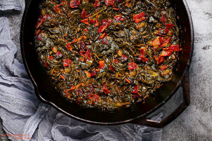 A close up shot of Braised Collard Greens with Bacon in a cast iron pot with a gray towel alongside.