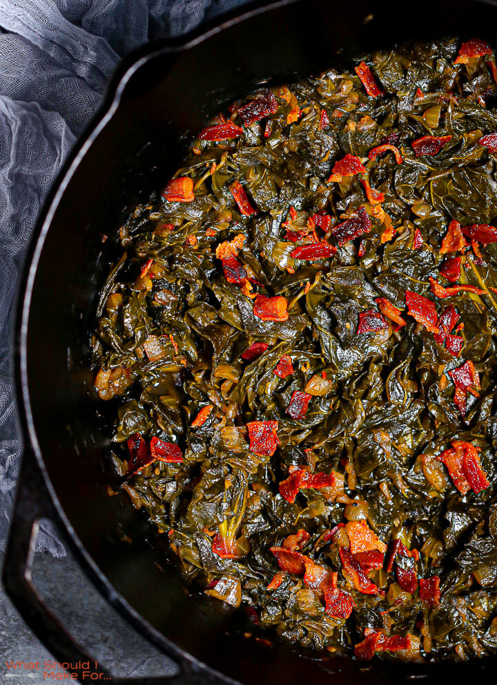 A close up shot of Braised Collard Greens with Bacon in a cast iron pot.
