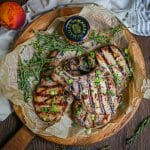 Mustard Glazed Grilled Pork Chops on a round wood serving board with fresh thyme sprigs and Maille mustard on the board.