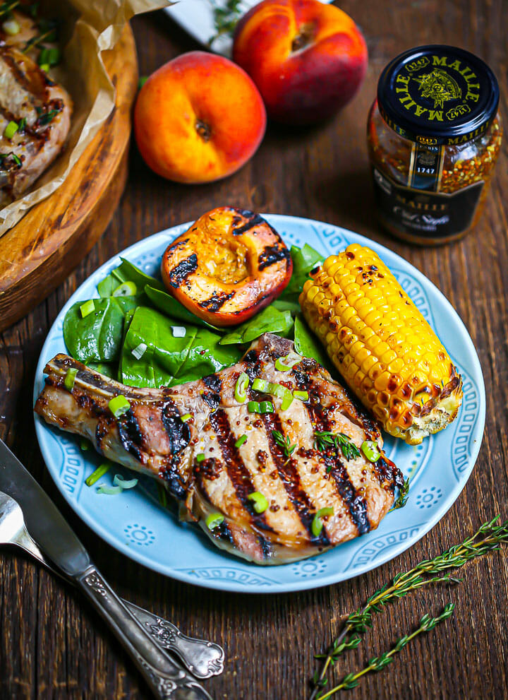 Mustard Glazed Grilled Pork Chops on a round wood board served with grilled peaches, corn, spinach, thyme and Maille mustard.