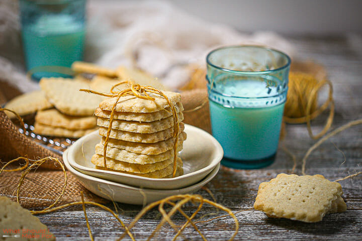 A stack of classic shortbread cookies on a wire rack tied with twine with a glasses of milk.