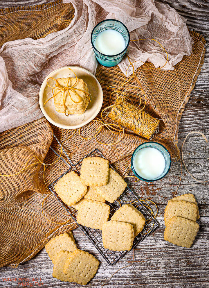 Classic Shortbread Cookies on burlap with a roll of twine, glasses of milk and a white towel.