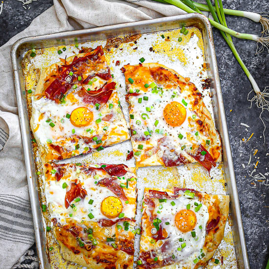 Ham, Egg and Cheese Breakfast Pizza golden, baked and sliced on a sheet tray.