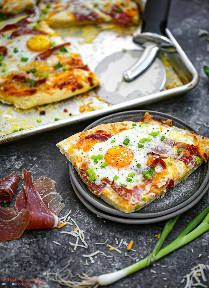 Ham, Egg and Cheese Breakfast Pizza golden, baked and one slice on a plate.