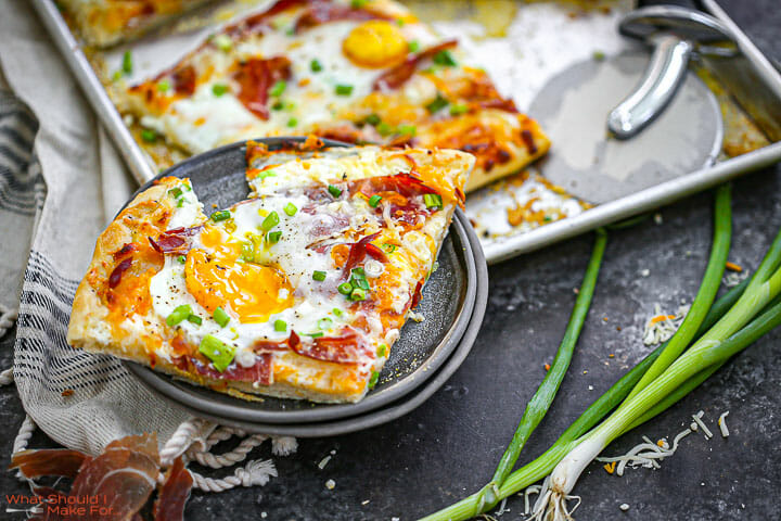 Ham, Egg and Cheese Breakfast Pizza golden, baked and one slice on a plate with the yolk running.