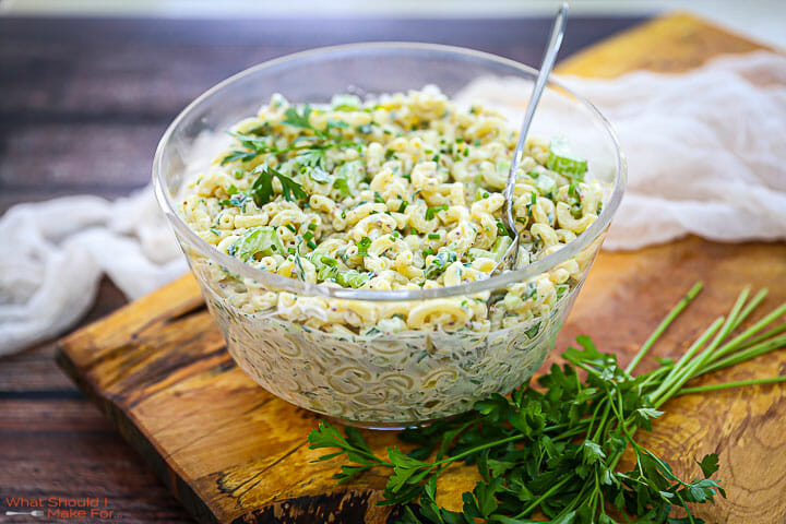 Classic Macaroni Salad in a glass bowl on a wood board garnished with parsley.