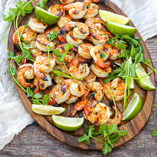 Margarita Grilled Shrimp on an oval wood platter with cilantro,lime wedges and a white table linen.