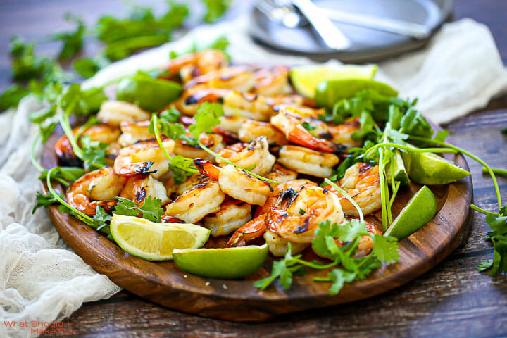 Close up of Margarita Grilled Shrimp on an oval wood platter with cilantro,lime wedges and a white table linen.
