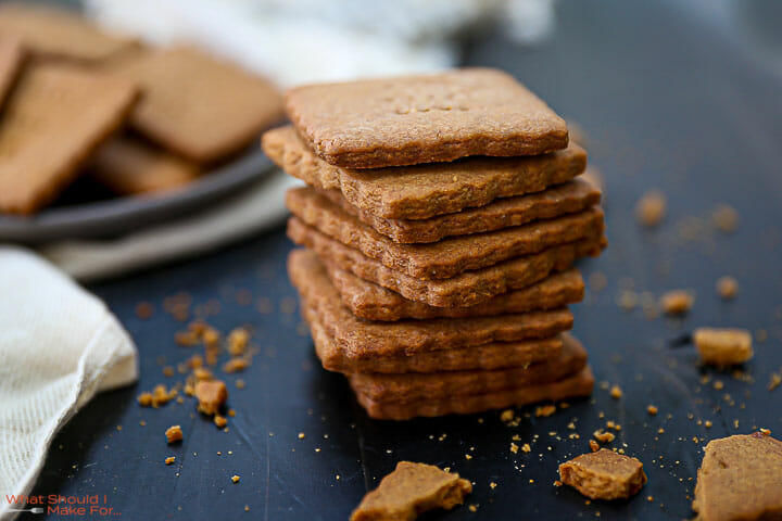 A stack of Homemade Graham Crackers on a black table top with crumbs scattered around.